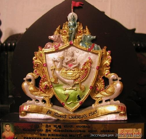 Это эмблема монастыря Содэ-матха, на которой изображен великий святой Вадираджа Тиртха. Вадираджа Свами жил в 16-ом веке, он достиг духовного совершенства и вознесся на небеса в летательном аппарате в форме божественной птицы, изображенной на данной эмблеме. Сверху - Удупи Кришна. Слева и справа - Хаягрива и Вараха - формы Господа Вишну, в которых Он покровительствует монастырю Содэ.