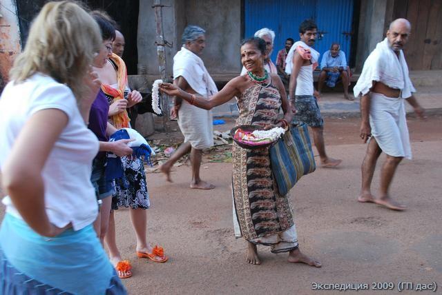 Женщины из племени лесных жителей предлагает купить цветочные гирлянды для подношения в храме