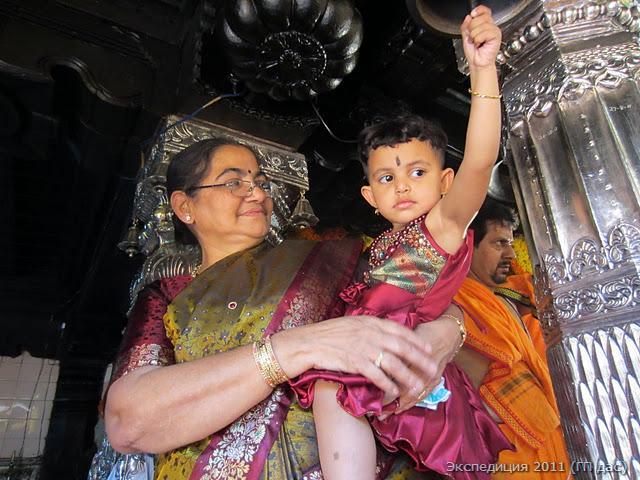 Бабушка с внучкой на празднике звонят в колокол